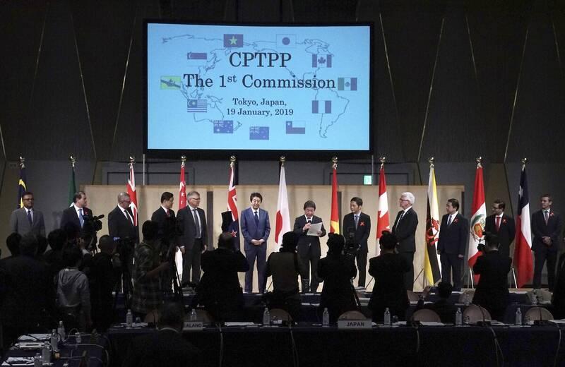 日本權威學者城山英已今天專文呼籲,日本應化被動為主動,支持台灣早於中國加入TPP。圖為2019年1月CPTPP會議在東京召開,各國領袖準備合影。中為時任日本首相安倍晉三。(美聯社)