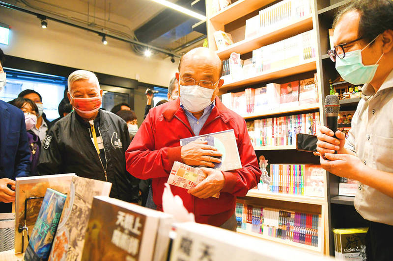 Premier Su Tseng-chang holds Triple Stimulus Vouchers in one hand and comic books that he plans to buy with the vouchers in the other during a visit to Taiwan Comic Base in Taipei yesterday. Photo: CNA