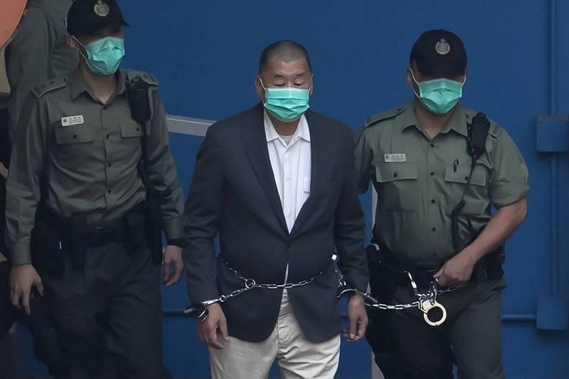香港壹傳媒創辦人黎智英被控違反「港版國安法」,遭警方以鐵鍊圍腰押送。(美聯社)
