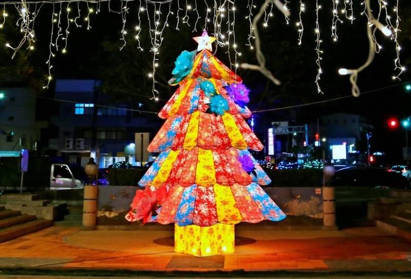 苗栗市公所客家花布耶誕樹出自新生代燈藝師李宗坤創作,高7公尺、寬4公尺,以藍、紅、黃、粉、紫色124塊客家花布拼接而成,外加8朵象徵富貴的牡丹花。(苗栗市公所提供)