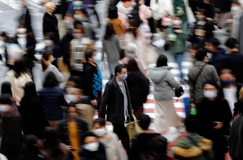 日本武肺疫情加劇,今天首都東京單日新增確診678人,再創疫情爆發後單日確診人數紀錄。圖為日本民眾戴著口罩穿梭東京街頭。(路透)