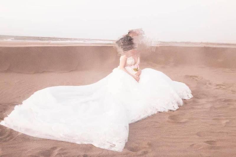 攝影師在沙地拍照,於起風時按下快門,網友直呼「你是風兒我是沙」。(圖取自爆料公社)