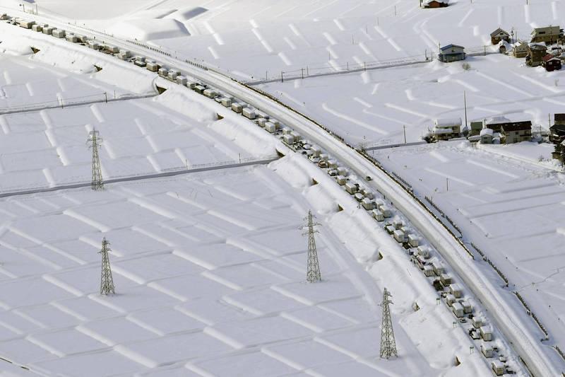 日本新潟自16日起,降雪量屢創紀錄,導致上千輛汽車受困於高速公路。(美聯社)