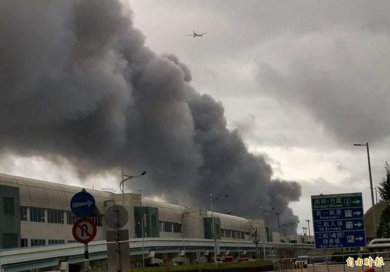 旭富製藥科技公司發生火警,濃濃黑煙像一條黑色巨龍盤踞在桃園機場北側跑道上空,出現「黑龍在天」的畫面。 (記者姚介修攝)