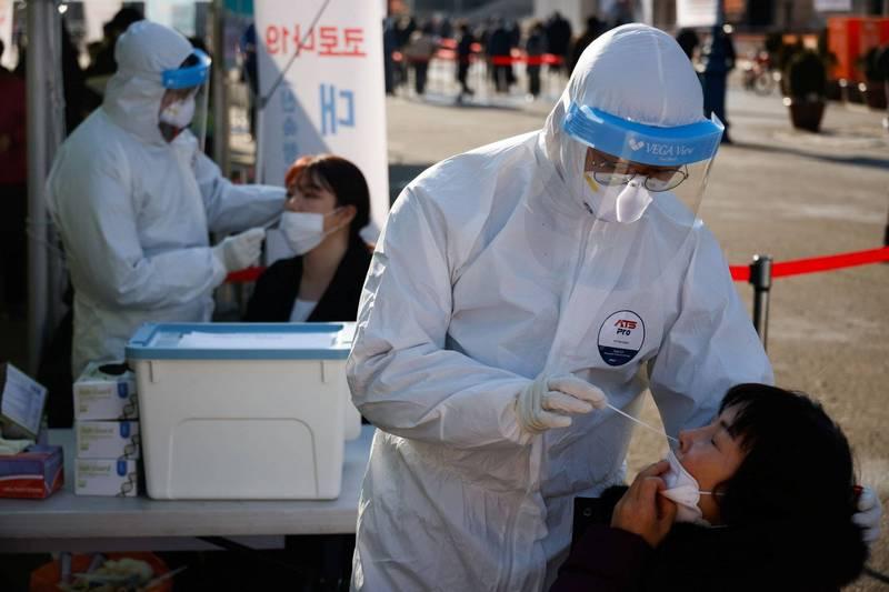 南韓宣布23日起首都圈禁止5人以上聚會;圖為南韓首都首爾一處車站外的武漢肺炎篩檢站。(路透)
