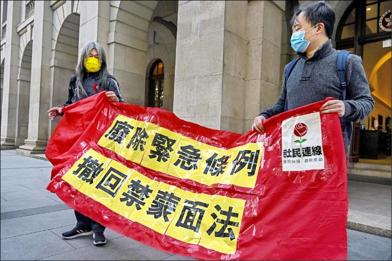 香港法院廿一日做出「终极裁决」,维持高等法院的上诉庭裁定。上诉人之一的香港泛民主派政党「社会民主连线」前立法会议员「长毛」梁国雄(左),在终审法院外拿布条抗议,要求香港政府废除紧急法,并撤回禁蒙面法。(法新社)(photo:LTN)