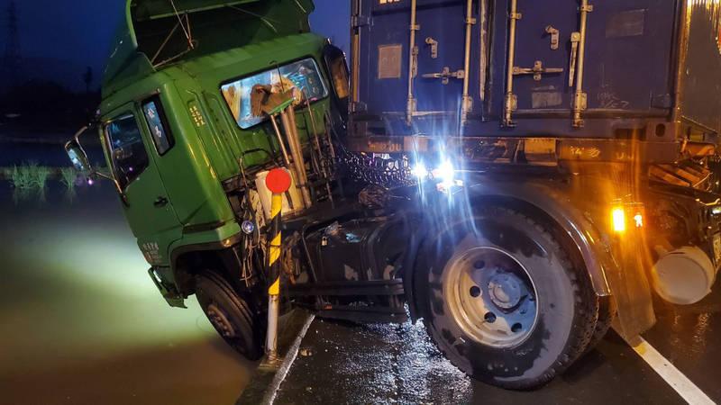 貨櫃車疑天雨路滑,不慎打滑,車頭卡在路旁水溝,警方封閉南下車道處理。(記者蔡昀容翻攝)