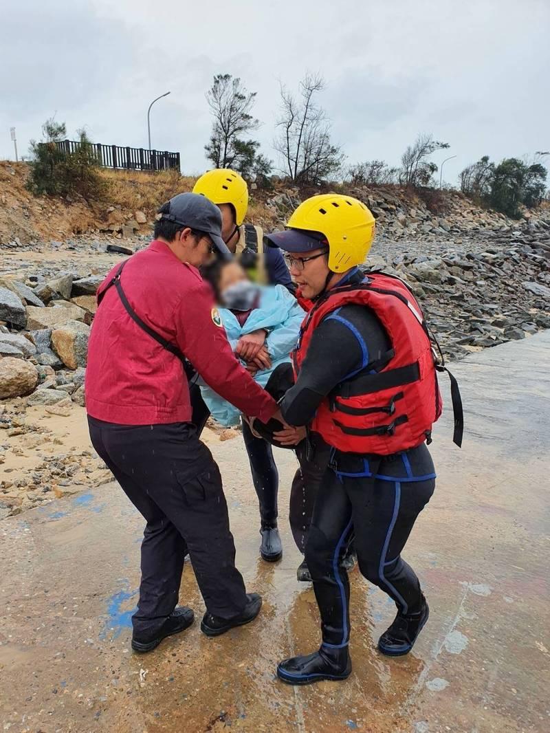 消防人員將徐婦搶救上岸,立刻以厚衣物包覆,以防失溫嚴重。(金門縣消防局提供)