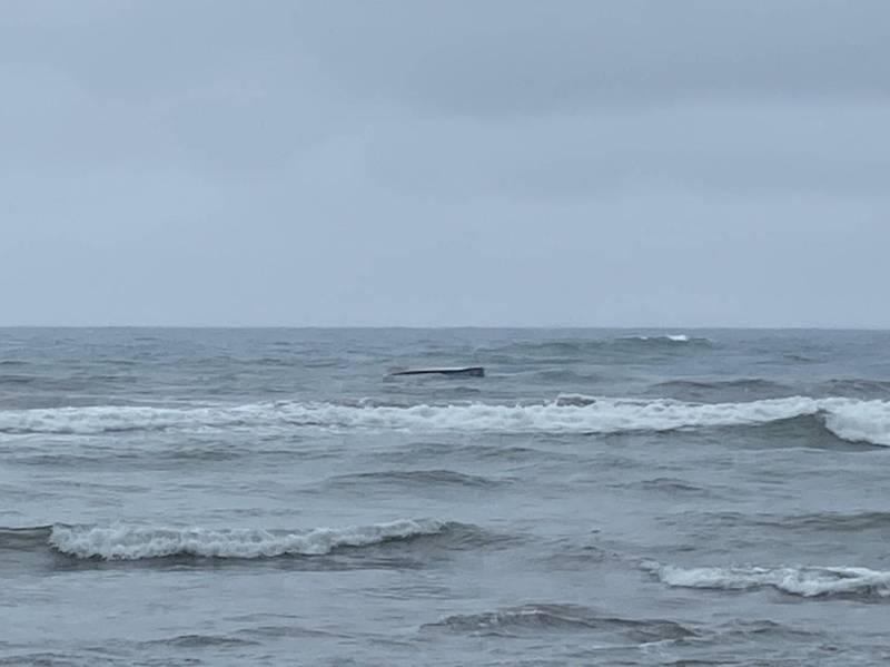 一艘舢舨今天上午在新北市金山區水尾漁港外遭突來大浪打翻。船上3名船員被及時趕抵的消防隊員與衝浪客救起。(記者林嘉東翻攝)