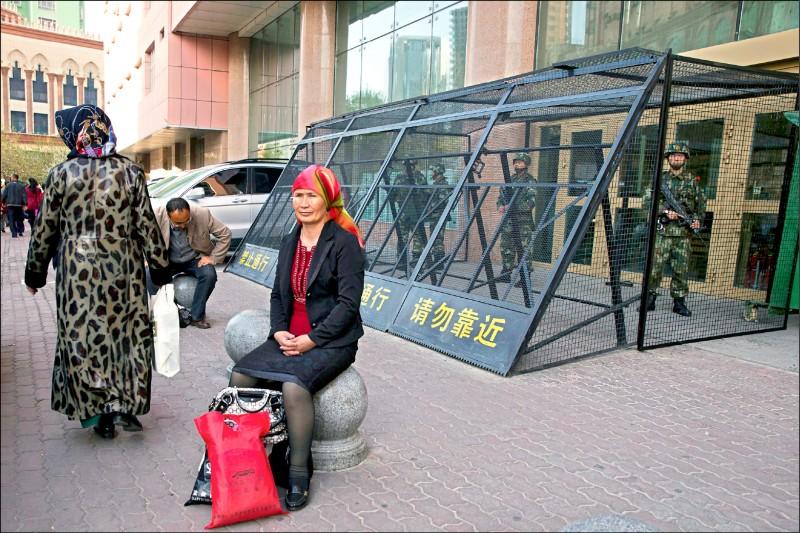二○一四年五月一日在新疆烏魯木齊市一名維吾爾族婦女,坐在保護駐地武警的金屬籠前。(美聯社檔案照)