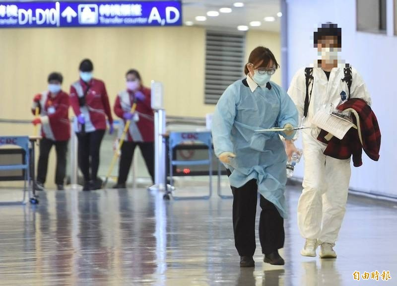 華航自英國倫敦飛返的班機傍晚降落桃園機場,其中一位旅客疑似有症狀,先行前往發燒篩檢站採檢,清潔人員在後立即清潔消毒。(記者劉信德攝)