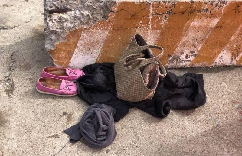 賴姓婦人將鞋、衣物及包包等放在岸邊。(記者歐素美翻攝)