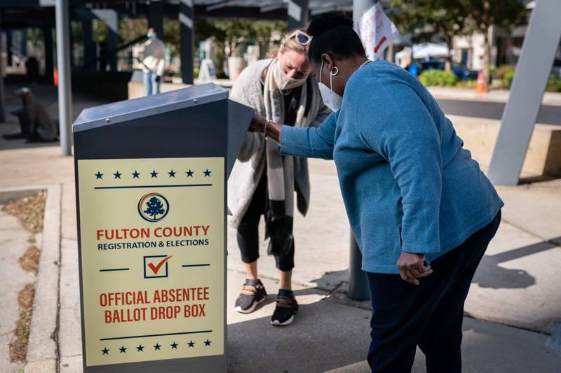 高等法院法官駁回了缺席選票投遞箱只能在辦公時間中使用的訴訟案。圖為喬治亞州富爾頓郡一位選務人員協助選民把選票投進缺席選票投遞箱一景。(彭博檔案照)