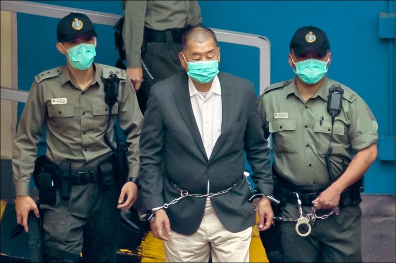 黎智英十二日遭控涉嫌違反港版國安法,被押往法院時,被拍到雙手遭銬上手銬、腰部被鐵鍊纏繞的畫面。(彭博)