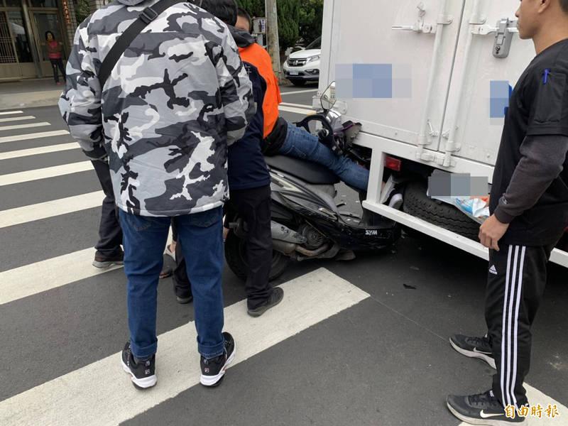 18歲女大生騎機車撞上停在路口卸貨的貨車,人與機車卡進貨車底盤。(記者陳鳳麗攝)