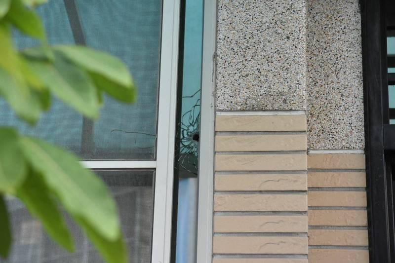 民宅玻璃被射出一個彈孔。(記者張軒哲翻攝)