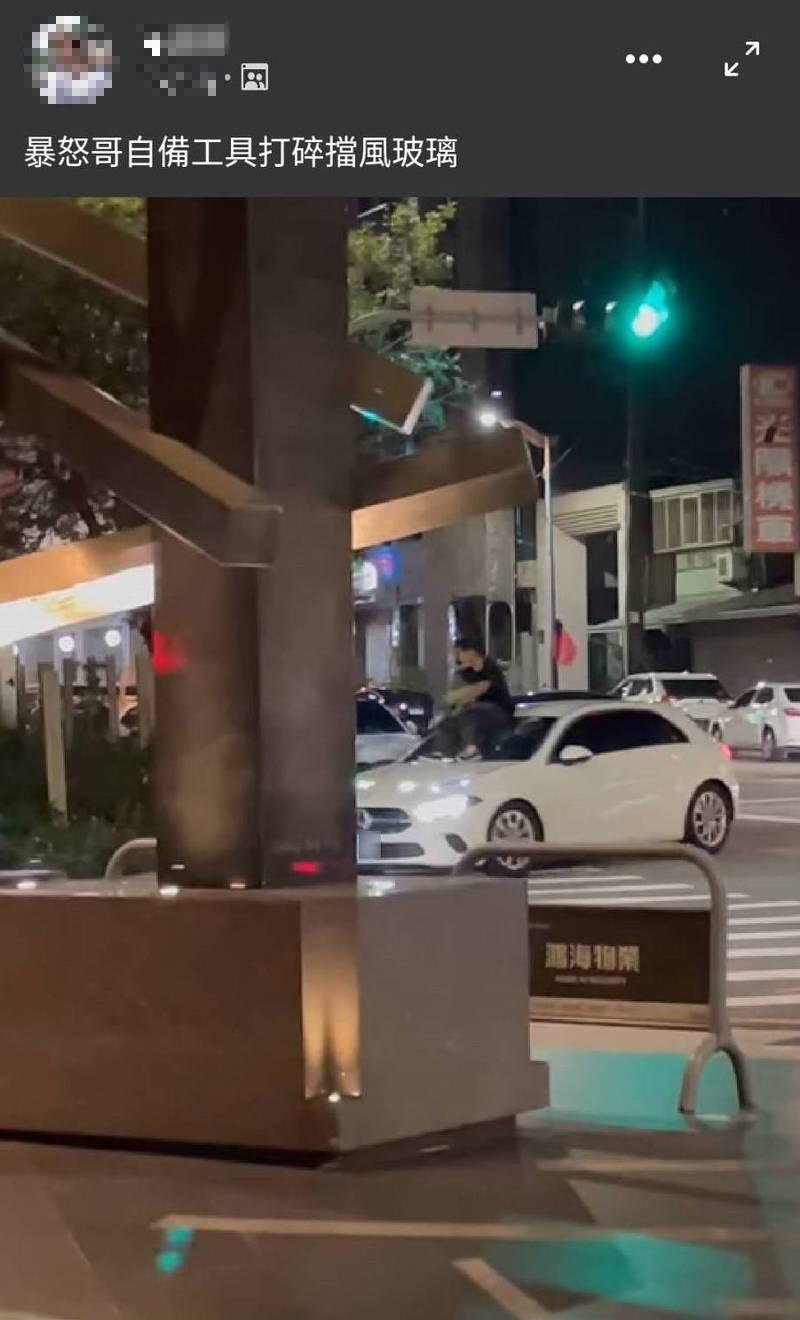 賴男疑似與妻子吵架,跳上妻子的白色賓士車,持工具怒砸擋風玻璃。(記者張瑞楨翻攝自臉書「爆料二社」)