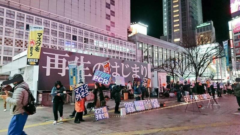 在疫情嚴重的東京,竟有一群人在街頭舉標語,呼籲路人「別戴口罩,露出笑容」,他們並稱,武漢肺炎出現,是為了淨化世界,讓世界「重生」。(擷取自推特)