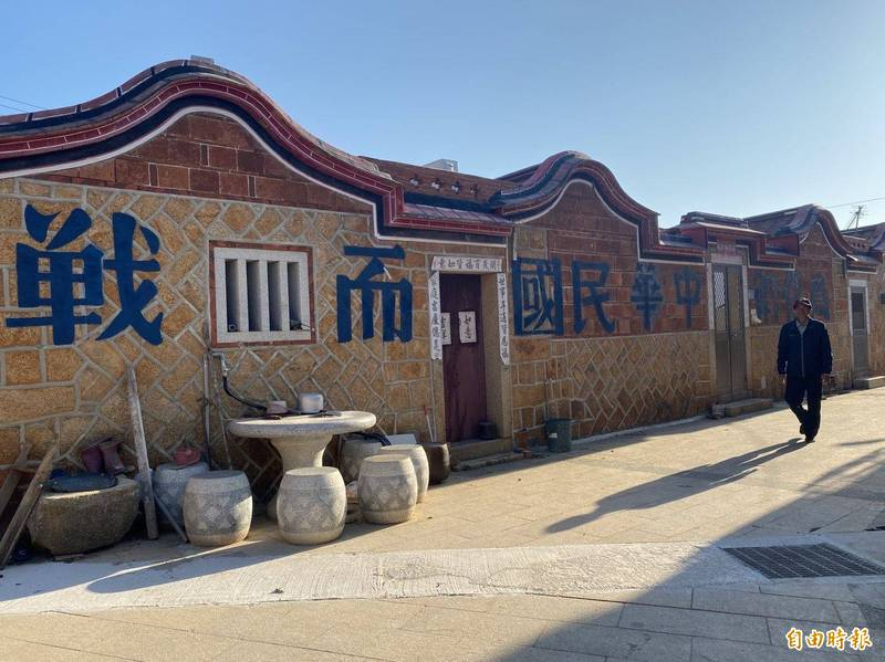 直接在長長的古厝牆面,重新為泥塑「為保衛中華民國而戰」的標語換上新漆。(記者吳正庭攝)