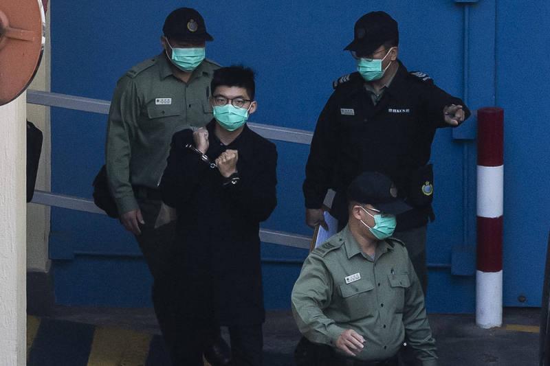 香港警方國安處人員今早展開大規模的拘捕行動,竟連正在服刑的前香港眾志秘書長黃之鋒也遭受波及。圖為先前黃之鋒遭押畫面。(法新社)