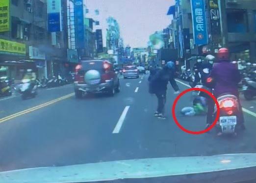 一名孩子(紅圈處)闖入馬路,被家長「一巴掌打趴」。(圖取自臉書社團「爆廢公社公開版」)