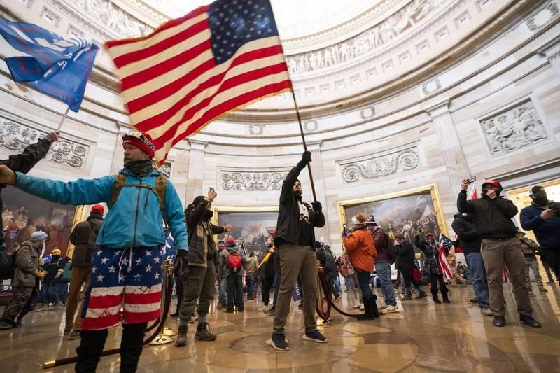 川普支持者在國會大廈內揮舞美國國旗和川普旗幟。(歐新社)