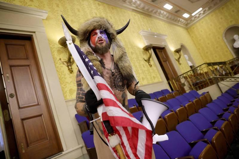 6日闖入國會參議院,頭戴牛角、披毛皮的示威者。(法新社)