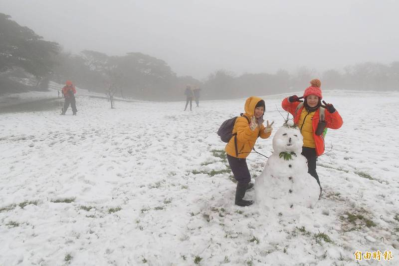 民眾身穿保暖衣物,在地上堆中型雪人。(記者張嘉明攝)