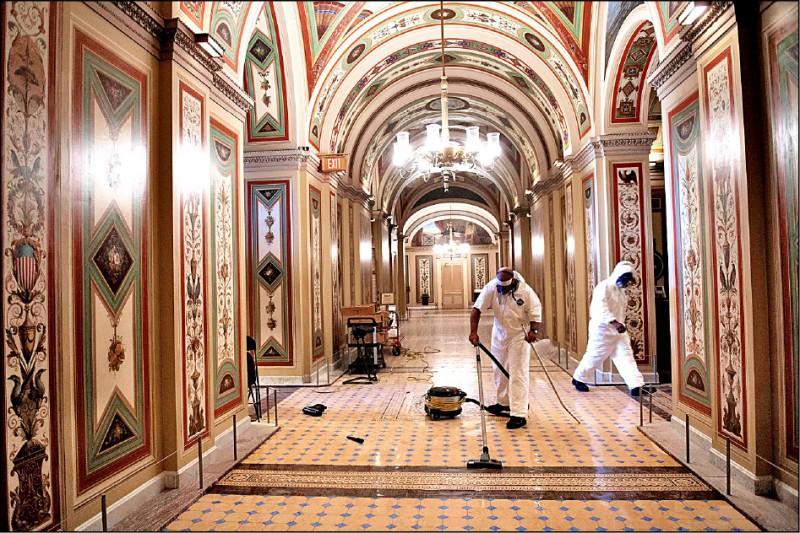 川普支持者6日闖入國會大廈內,清潔人員7日趕忙進行清理和消毒工作。(法新社)