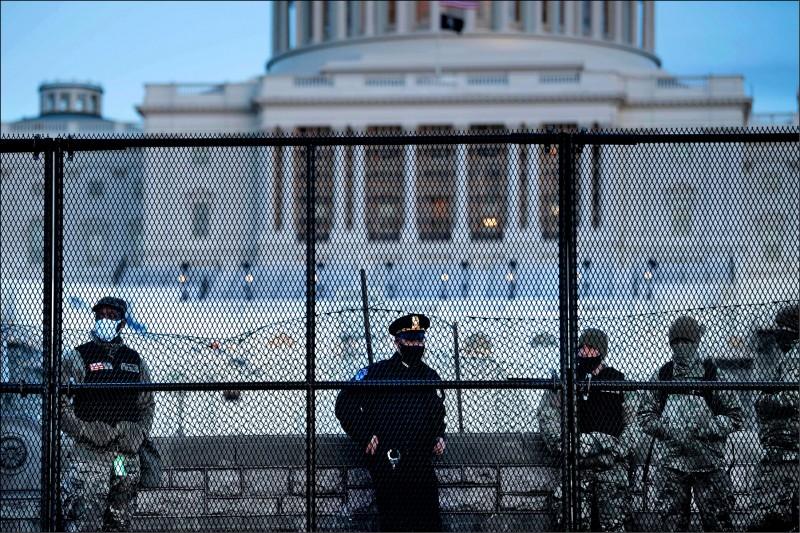 專責美國國會山莊維安的國會警察與增援的國民兵,七日在國會周遭架起圍欄及鐵絲網,嚴防國會可能再遭攻擊。(法新社)