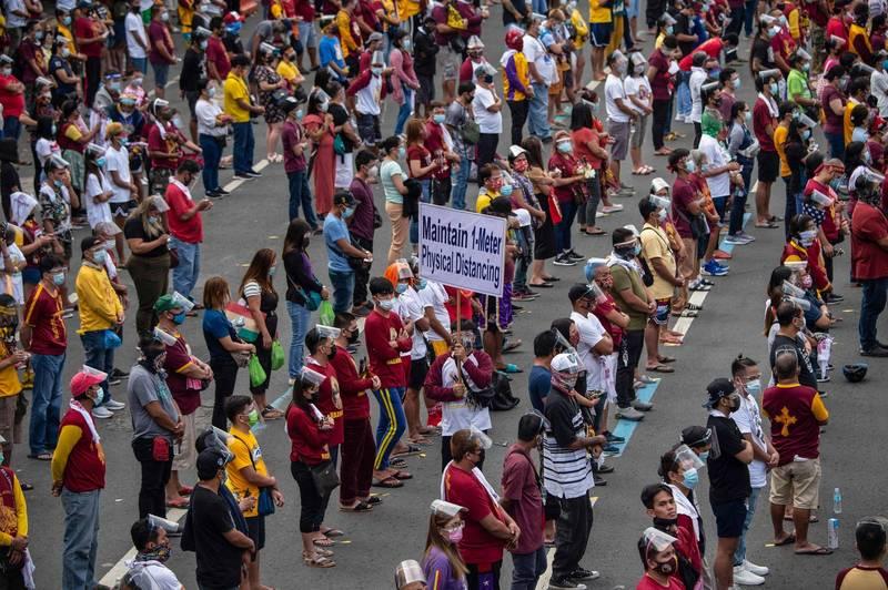 菲律賓萬人朝聖「黑拿撒勒人」,當局也加派警力確保民眾維持至少1公尺的社交距離。(法新社)