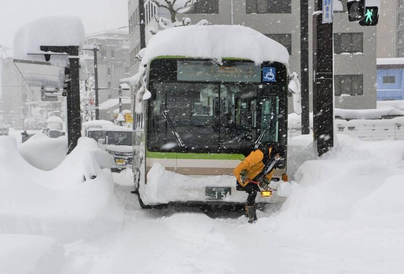日本靠日本海側的地區連日大雪紛飛,圖為日本富山士公車受男於大雪的畫面。(美聯社)