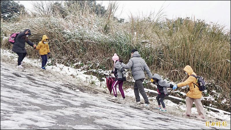 不少遊客上大屯山賞雪,不過由於路面結冰濕滑,遊客必須注意踏穩步伐,不少民眾不慎滑倒,也有遊客索性手腳併用用爬行方式上山。(記者劉信德攝)