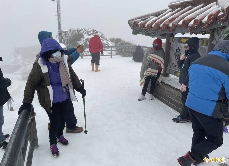 合歡山今晨再度飄雪,一片雪白,賞雪遊客興奮在武嶺亭地標拍照留念。(記者佟振國攝)