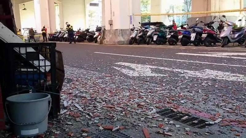 基隆市華三街成功國宅外牆磁磚掉滿地,彷彿下起「磁磚雨」。(記者林欣漢翻攝)