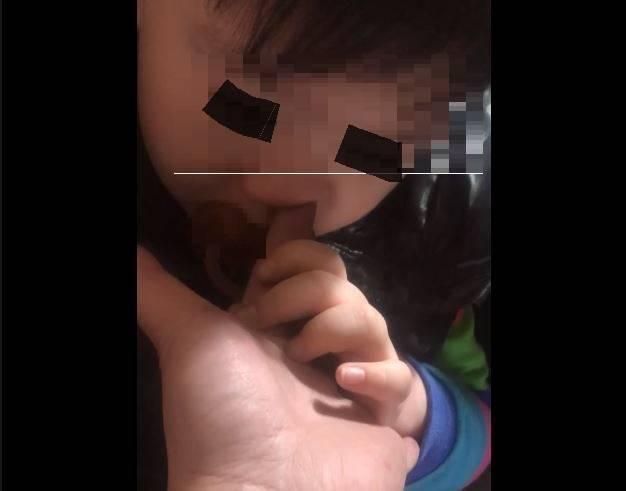 5歲小兒緊抓著媽媽的大手,把媽媽食指直直地插入自己的右邊的小鼻孔。(圖擷取自爆怨公社)