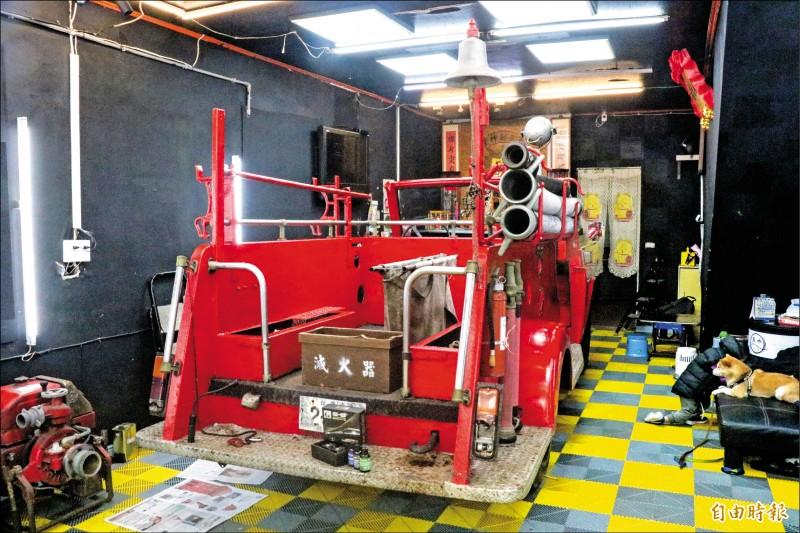 消防車的車尾右側掛有警鐘,中間擺放裝滅火器的木箱及摺疊擔架。(記者蔡昀容攝)