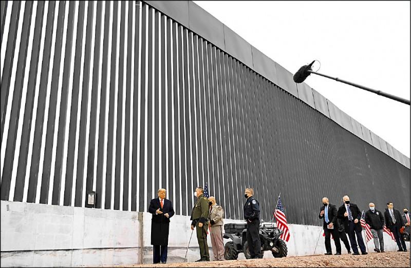 美國總統川普十二日訪問德州,在他力推的美國和墨西哥邊境「川普牆」銘牌簽名。(法新社)