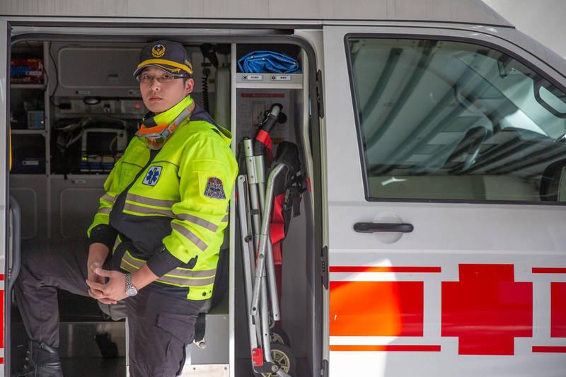 新店分隊消防員張楚騰接獲米店老闆通報,在救護車上緊急給予婦人藥物,緩解急性心肌梗塞症狀。(記者闕敬倫翻攝)