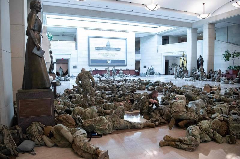美媒本周三進入國會大廈,發現大量國民兵正在執勤,或在大廳、走廊席地而睡,與穿梭其中的國會議員形成對比。(法新社)
