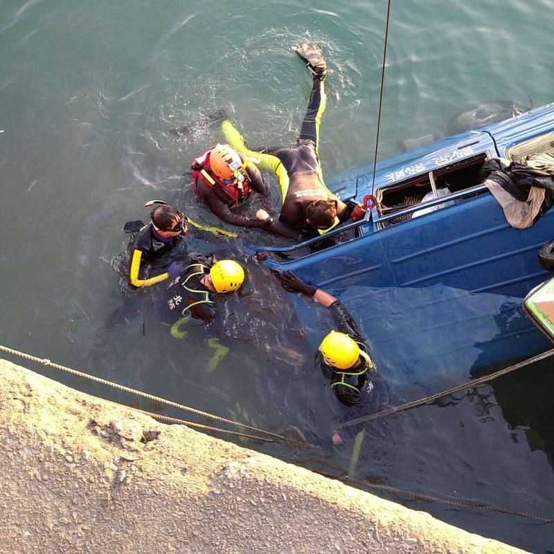 消防人員下水搶救衝入漁港的箱型車。(記者徐聖倫翻攝)