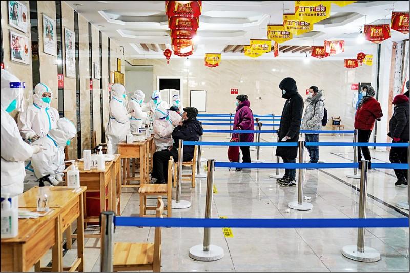 黑龍江省成為中國疫情的第二個重災區。圖為哈爾濱市衛生人員為民眾採檢。(法新社)