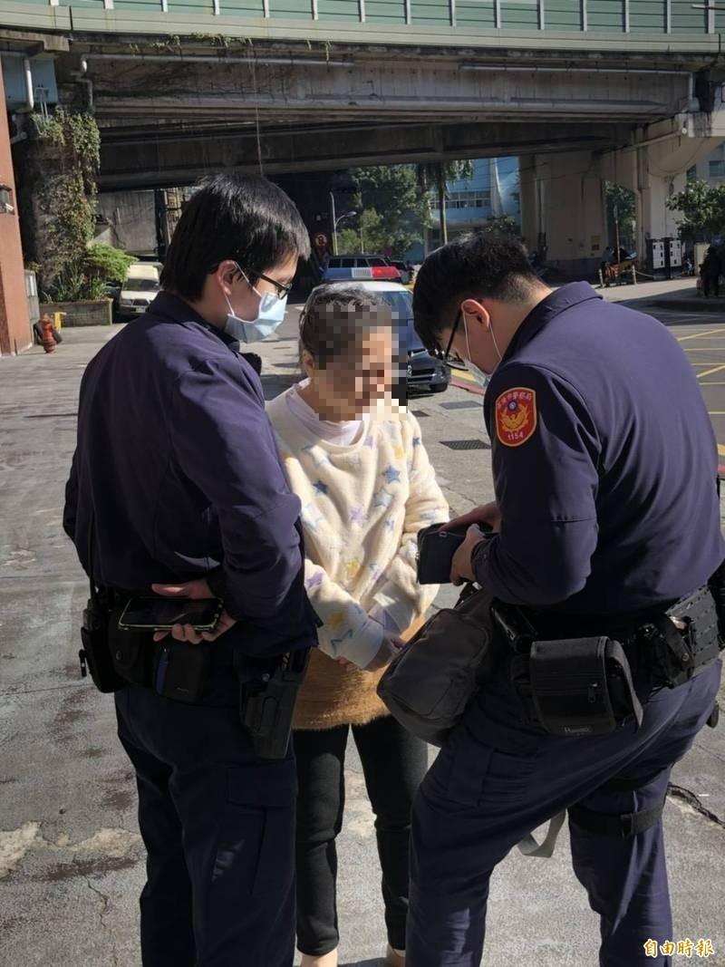 江姓婦人沒戴口罩硬要上車,警方獲報到場將她勸導下車後,查驗她身分。(記者林嘉東攝)