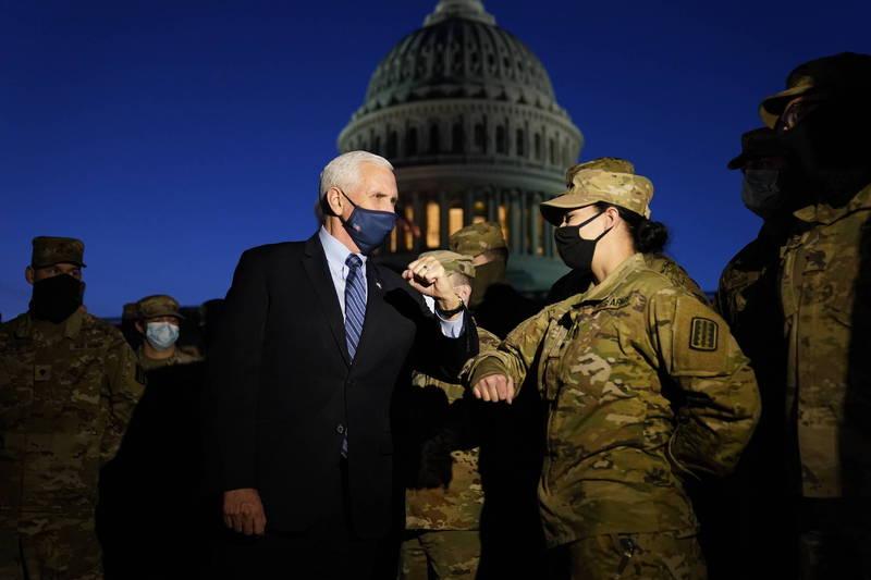 美國副總統彭斯(Mike Pence)14日在國會大廈外與數十名國民兵會面。(美聯社)