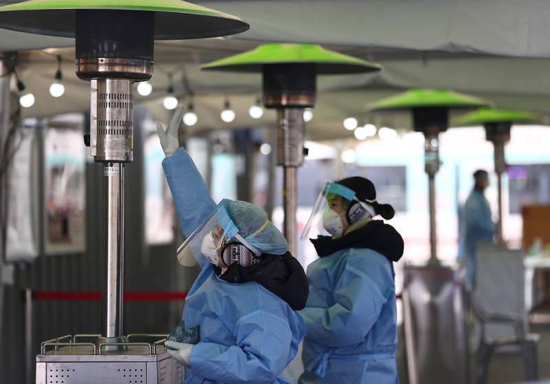 南韓疫情延燒,當局延長防疫響應,並訂立「春節特別防疫期」。圖為正在暖手的首爾站防疫人員。(歐新社)