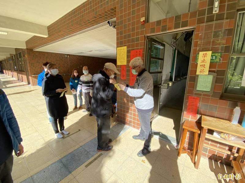 119投票所前選民排隊量體溫,等候進入投開所領、投票。(記者陳璟民攝)