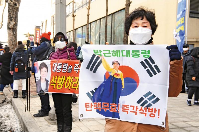 南韓最高法院14日宣判,前總統朴槿惠貪腐案,維持高等法院重判20年有期徒刑的判決。其支持者當天在院外舉牌,除主張國會和憲法法院2018年對朴槿惠的彈劾無效外,也要求立刻釋放她。(歐新社)