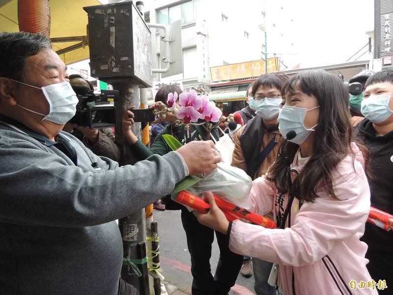 黃捷到傳統市場送春聯拜年,花攤回贈蘭花,讓黃捷好開心。(記者王榮祥攝)