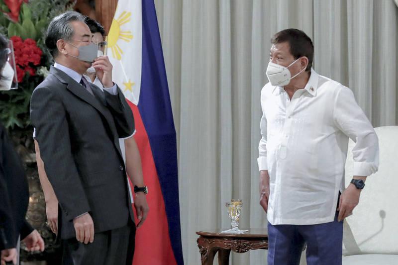 中國外交部長王毅近日到訪菲律賓,與菲律賓外交部長陸辛及總統杜特蒂會面,雙方承諾將攜手重建經濟,圖為王毅(左)與杜特蒂(右)。(美聯社)