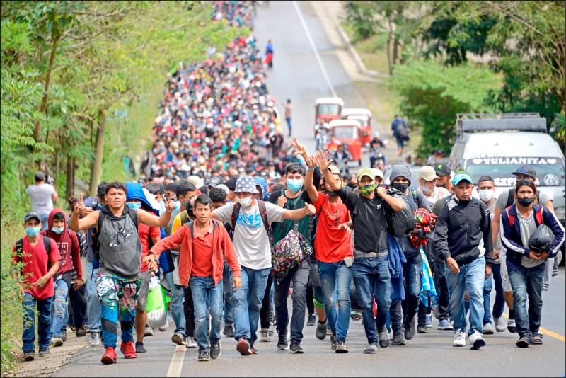 二○二一年首波從宏都拉斯出發、一路往北欲闖關入境美國的宏國無證移民隊伍,人數至少九千人,已進入其鄰國瓜地馬拉。圖為這批移民十六日在瓜國奇基穆拉省卡莫坦的公路上行走,長長的人龍看不到盡頭。(法新社)